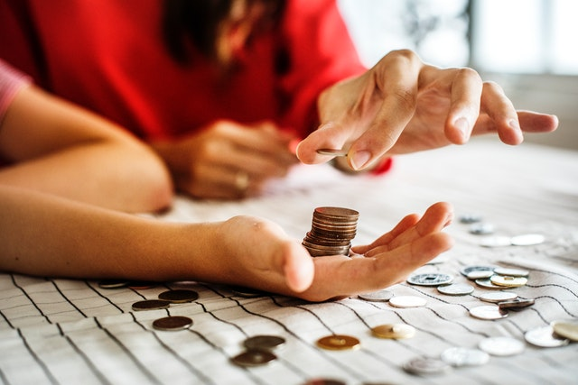 lady stacking up coins on her palm
